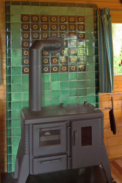 Stangenherd in einem Holzhaus mit Hitze-Kacheln.